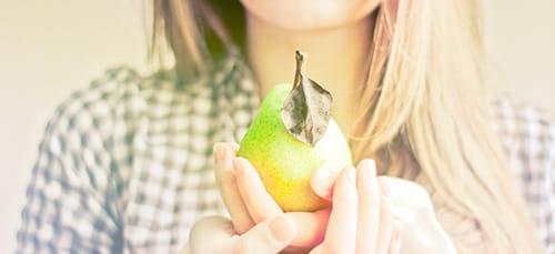 девушка держит грушу