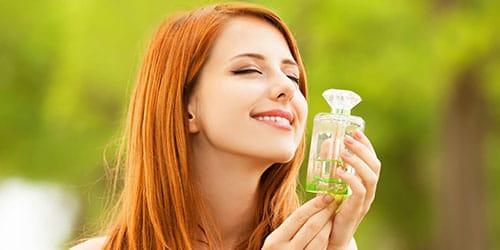 девушка держит парфюм
